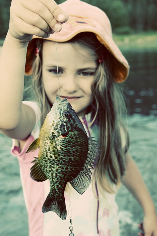 close up of little girl holding a string of the caught fish