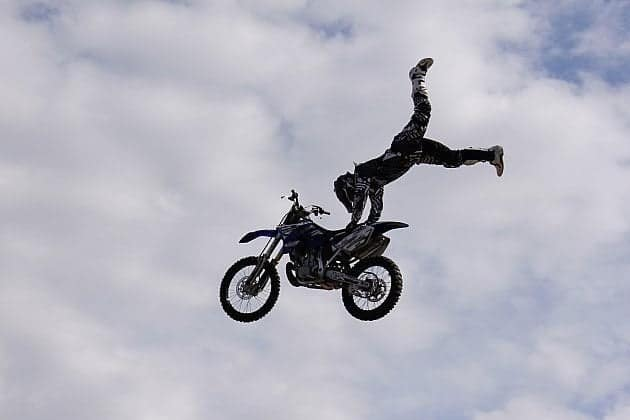 doing a handstand on the seat of the flying motorbike