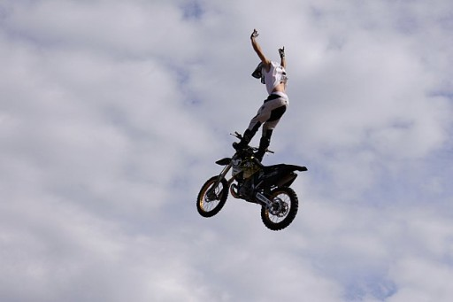 Standing on the handlebars of their flying motorbikes