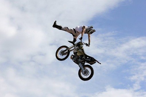 doing a handstand on the handlebars of the motorbike while on the air