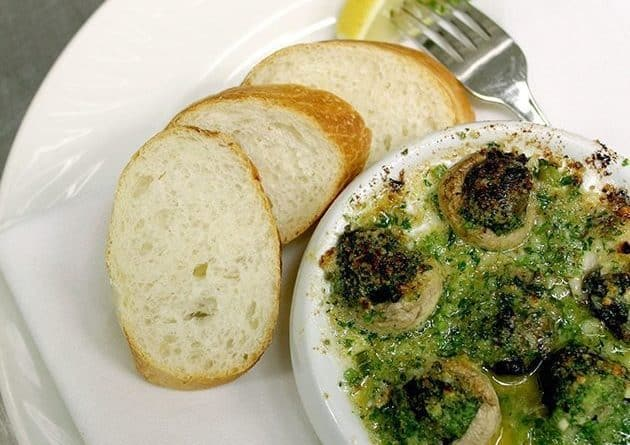 close up of Escargot Forestiere with garlic and melted butter, slices of French bread on side garnish with a slice of lemon at parsley