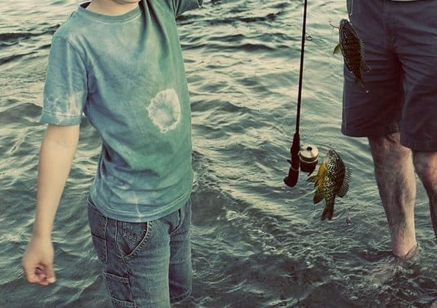 kid holding his small catch fish