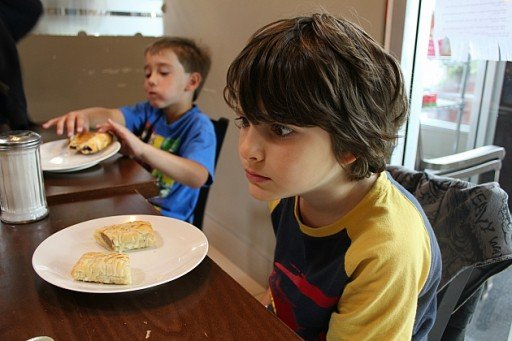 white plate with two sausage rolls on the table in front of a boy
