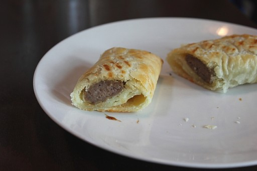 close up of white plate with two sausage rolls