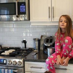 little girl in red sleeping pajamas sitting on top of the kitchen table