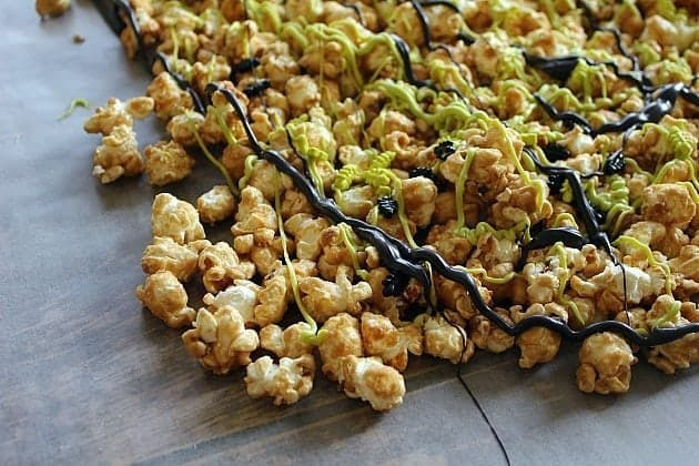 Melted green and black chocolate disks drizzled all over the popcorn