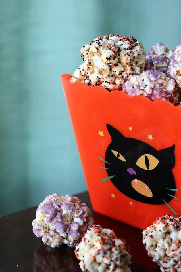 Spookily Sprinkled Popcorn Balls in a red pop corn container designed with a black cat