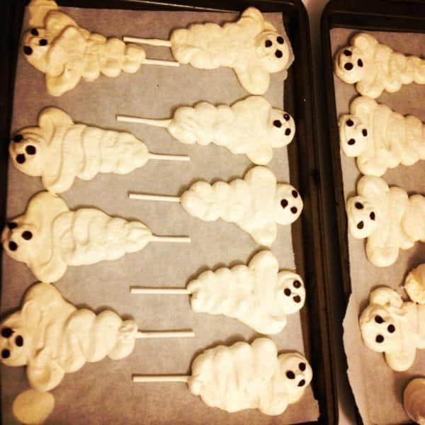 Meringue Halloween Treats lined in baking sheet with parchment papers