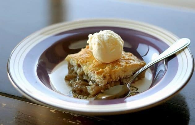 a slice of PEAR COBBLER vanilla ice cream on top on a blue designed plate