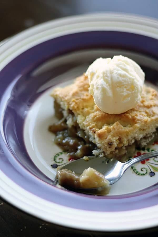 close up of a slice of PEAR COBBLER topped with vanilla ice cream on a blue designed plate