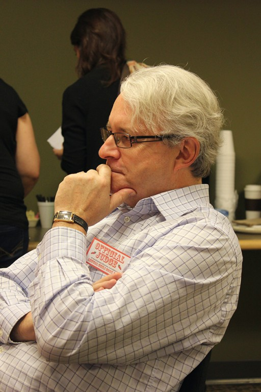 man with eye glasses and white hair, sitting while holding his chin