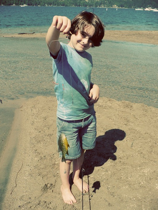 little boy near the lake water holding a string with a fish in it