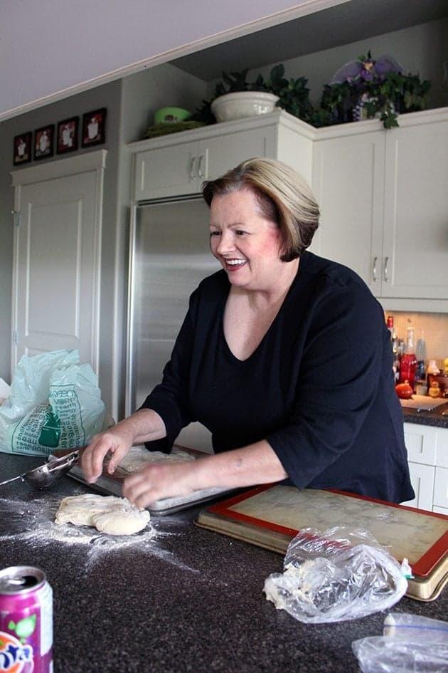 a woman in the kitchen preparing a dough
