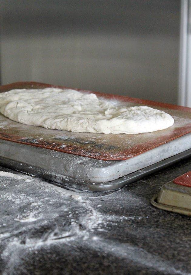 big pizza dough in pizza tin