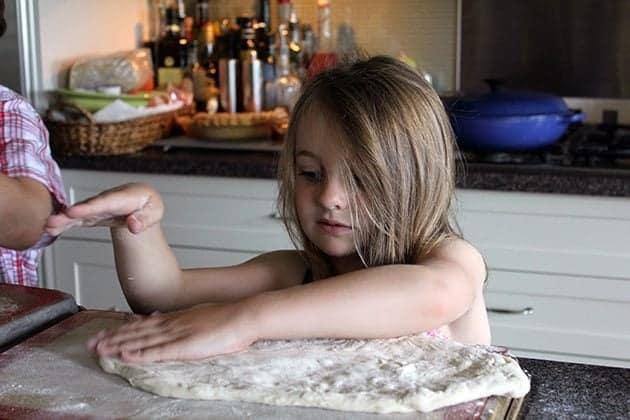 little girl flattening the dough