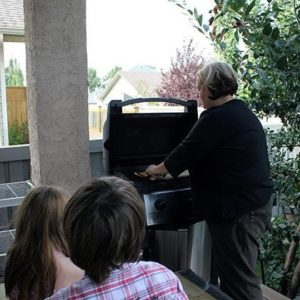 a woman cooking the pizza while two kids were sitting and watching her