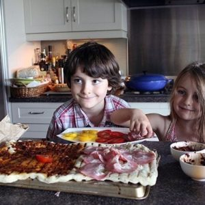 two kids adding the pizza sauce and toppings to the big dough