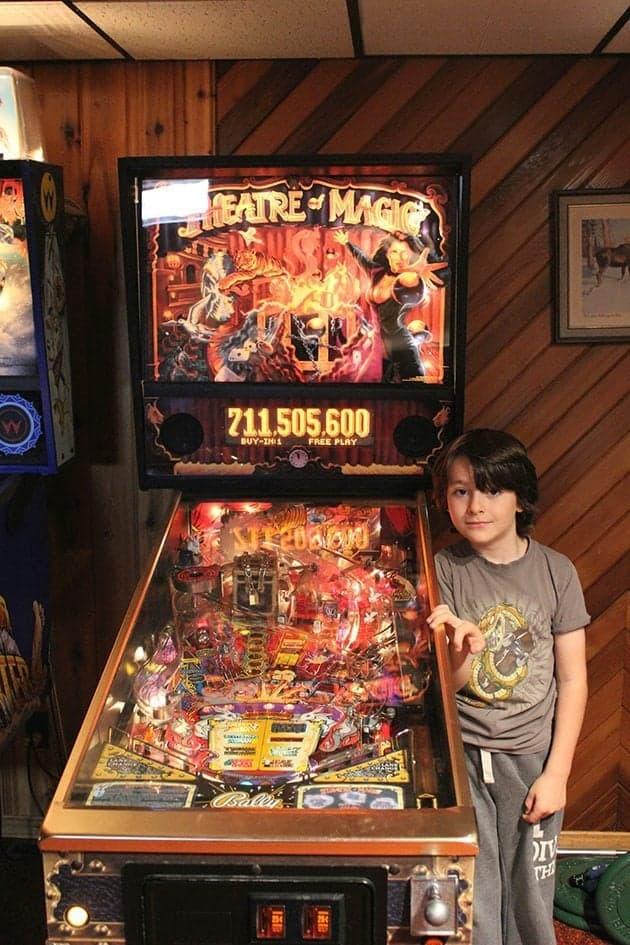 little boy standing beside the pinball machine