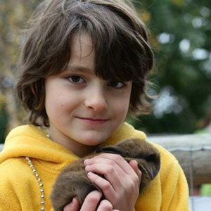 close up of a little boy wearing yellow jacket