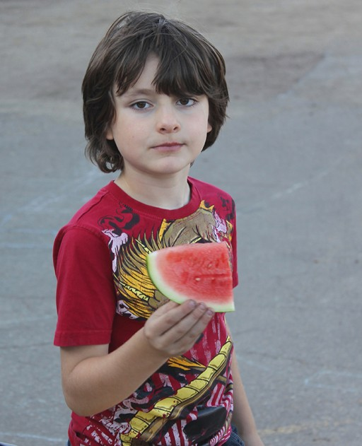 little boy wearing red shirt holding a slice of watermelon