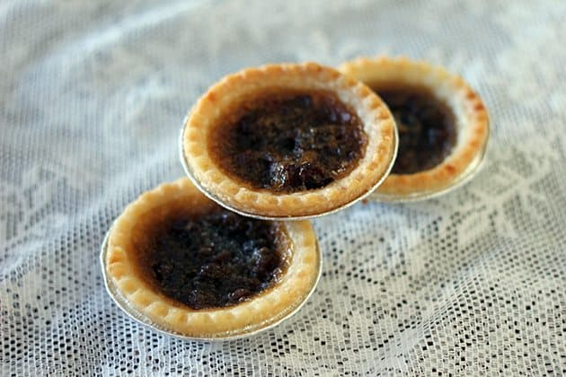 close up 3 pieces Butter Tarts with raisins on a white floral tablecloth background
