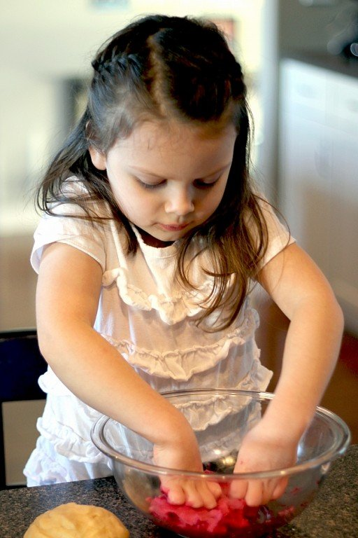 little girl wearing white busy with the mixing bowl