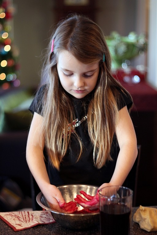 little girl with hands colored red inside the mixing bowl