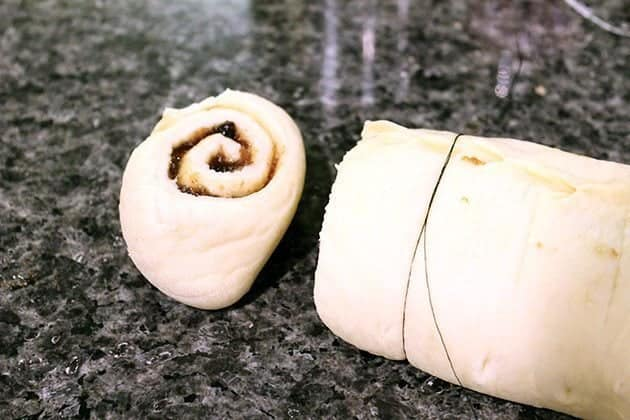cutting the rolled up Rum Glazed Mincemeat Cinnamon dough