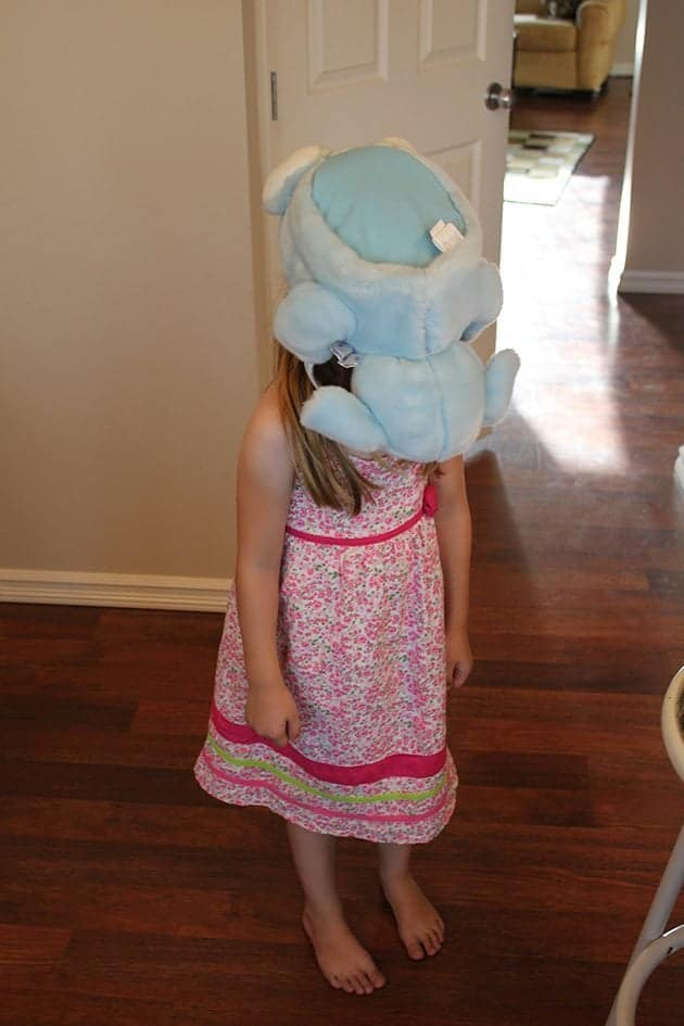 little girl with a stuff toy on her head and face