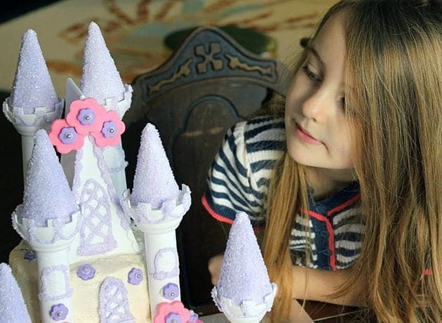 little girl with long blonde hair staring at the castle cake