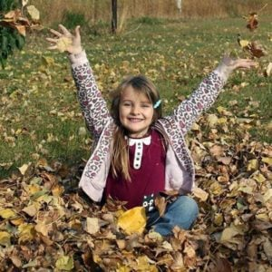 little girl sitting in a bunch of dry leaves