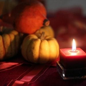 close up of pumpkin decors and square lighted candle on the table