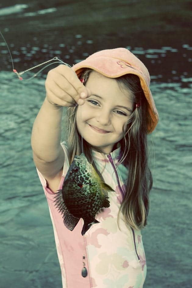 cute little girl holding a string with fish in it