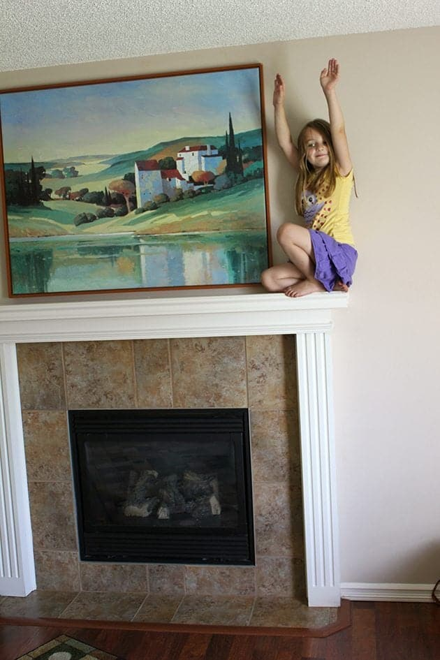 little girl on top of the fireplace near the wall painting