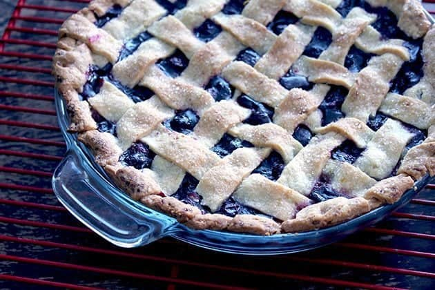 blueberry pie with lemony lattice top in a Pyrex pie pan on red cooling rack