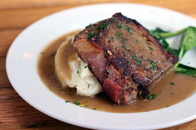 Pleasant Creek ranch beef, lamb & pork with creamy decadent mashed potatoes and a side of sautéed spinach in a white plate