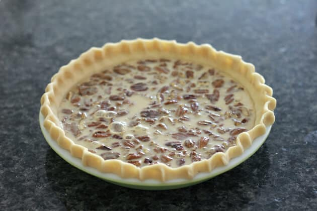 pie shell with mixture in it over the walnuts