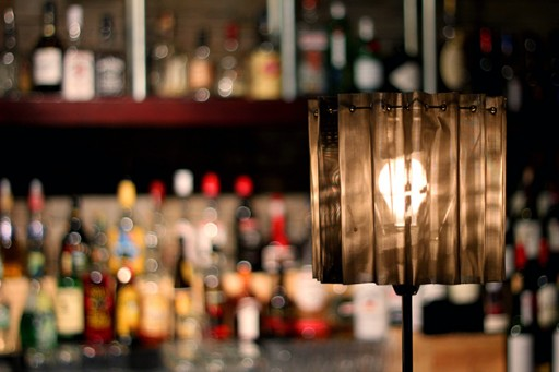 lighted lampshade with the lots of wine bottles at the background