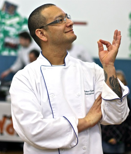 male chef in white uniform with one hand in OK gesture