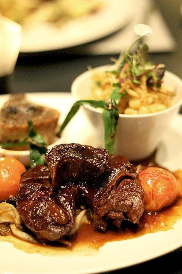 braised veal leg, macaroni and cheese, grilled green onions, Campania tomatoes, and wild mushrooms