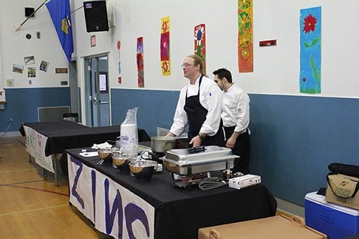 the Zinc table with two male chefs wearing black kitchen apron