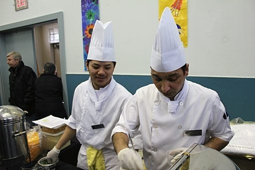 two chefs wearing white uniforms are busy in the kitchen