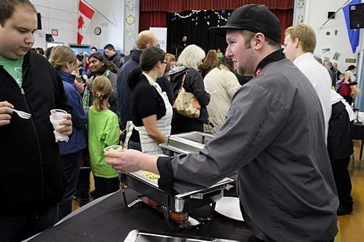 a man handing out a cup of mac n' cheese to a participant