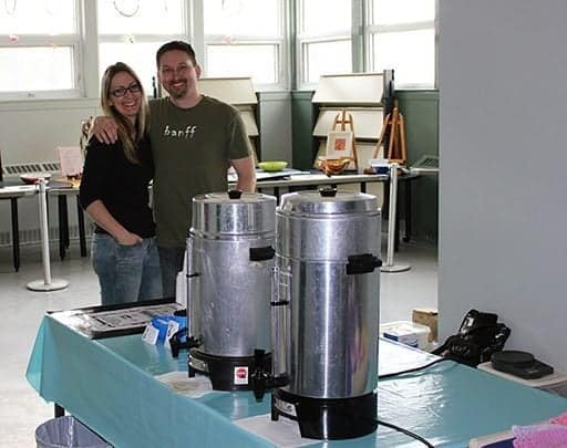 couple standing in the kitchen, two coffee dispensers on top of the table