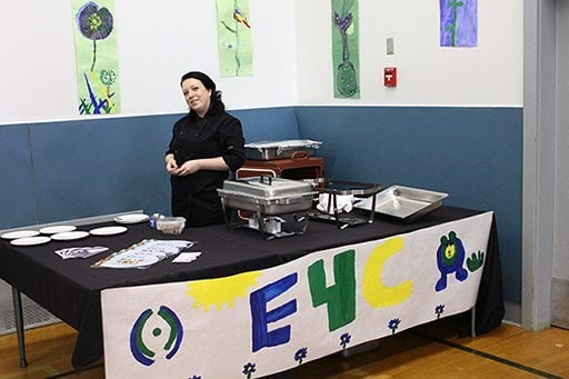 set up of E4C's table with a woman wearing all black standing beside it