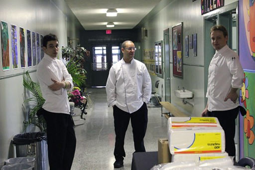 three chefs wearing white uniform are chatting in the pathway