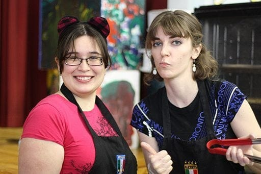 close up shot of two women wearing pink and blue with one holding a red kitchen tongs