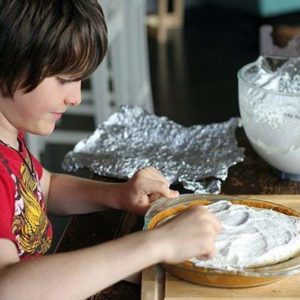 A boy Spreading the filling on top of the Pie from glass container
