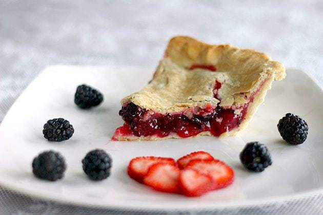 slice of strawberry pie in a white plate with some fresh strawberry slices and blackberries