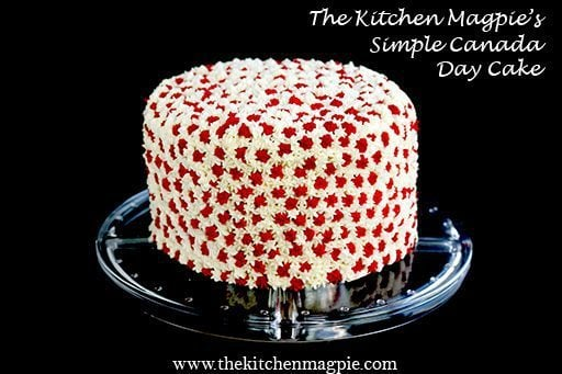 Canada Day Cake with red and white star icing on a clear cake stand
